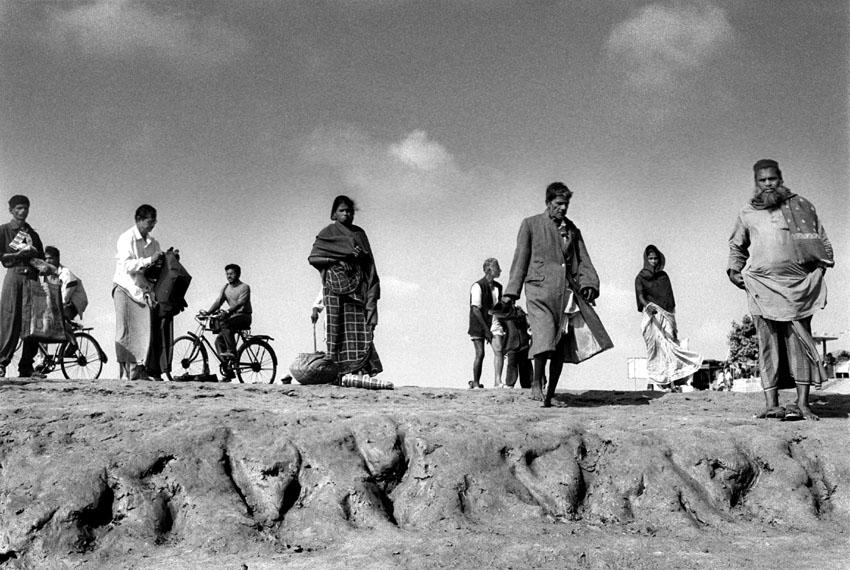 India, Sundarban, 200302.  After traveling for hours people come back from Kolkata's suburbs where they work as day labourers or sell their vegetables on the market. Before they reach home they have to cross the water several times that separates the islands . At low tide they can move on by foot for some time. Sundarban-eilanden spreiden zich uit de delta ten zuiden van Kolkata in de baai van Bengalen tussen India en Bangladesh.  Het gebied is moeilijk toegankelijk, heeft weinig basis-voorzieningen. De landbouwgrond per gezin is door de overbevolking te schaars geworden om in het levensonderhoud te voorzien. Mensen vluchten naar de stad of putten het kwetsbare ecosysteem uit met illegale visvangst, houtkap...  Mensen komen uit Kolkata na gedane arbeid. omdat het laagtij is kunnen  ze een eind te voet  door het water