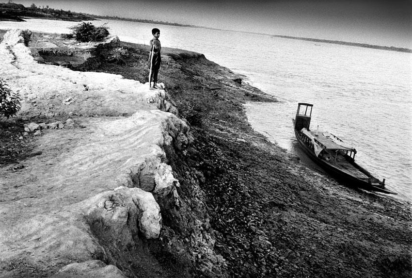 India, Sundarban, 200302.  A boy on the edge of the inhabited world. the isles that spread at the horizon are the territory of the Bengal tiger, who sometimes seeks his refuge on the other islands as humans exhaust his own food supplies. Sundarban-eilanden spreiden zich uit de delta ten zuiden van Kolkata in de baai van Bengalen tussen India en Bangladesh.  Het gebied is moeilijk toegankelijk, heeft weinig basis-voorzieningen. De landbouwgrond per gezin is door de overbevolking te schaars geworden om in het levensonderhoud te voorzien. Mensen vluchten naar de stad of putten het kwetsbare ecosysteem uit met illegale visvangst, houtkap...  Een jongen op de rand van de door mensen bewoonde wereld. De volgende eilanden zijn het territorium van de Bengaalse tijger, die zijn voedsel steeds vaker op de andere  eilanden zoekt omdat mensen zijn voedingsbronnen uitputten.