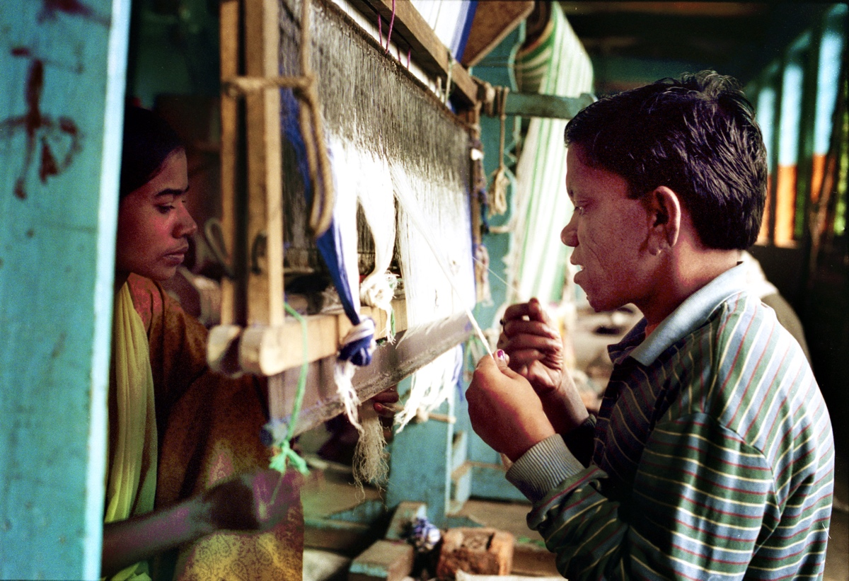 A boy and a girl work at the handloom after having been treated in time, so their mutilations are not very much visible