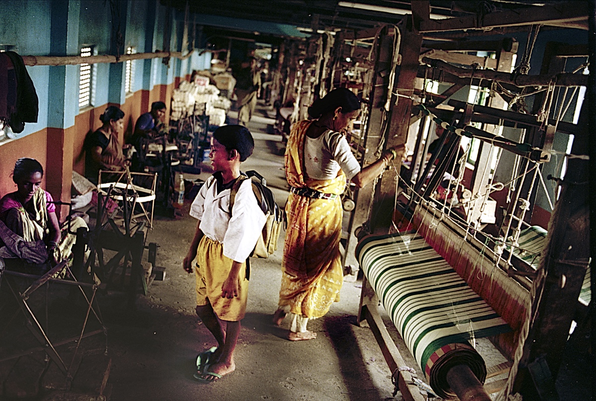 Before he goes to school a boy looks for his mother who is busy weaving. The uninterrupted noise of the handlooms is to be heard in the vicinity